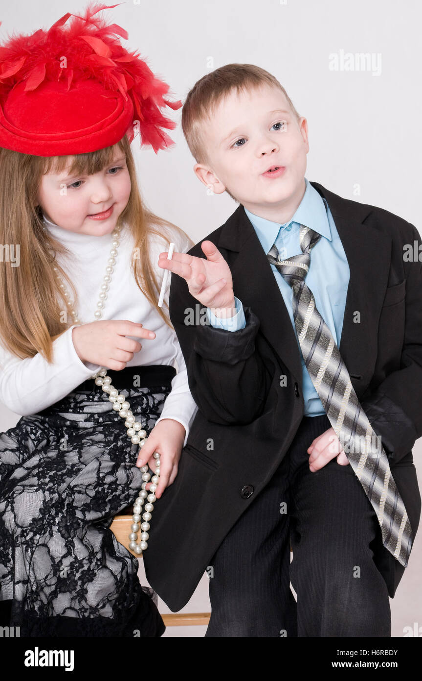cigarette lady hat boy lad male youngster smoker whiff smoke smoking child girl girls suit cigarette skirt blouse - Stock Image