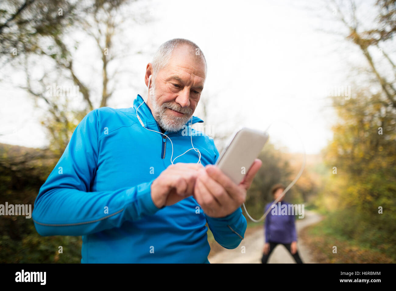 Senior runners in nature, stretching. Man with smartphone with e - Stock Image