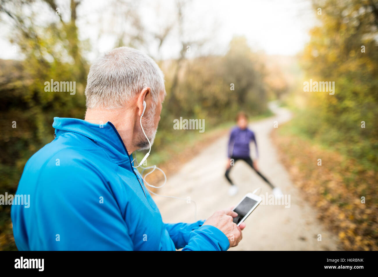 Senior runners in nature, stretching. Man with smartphone with e Stock Photo
