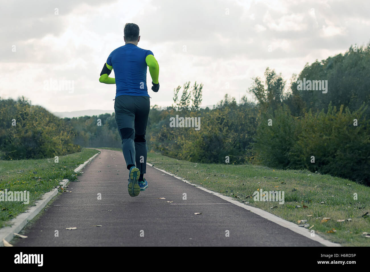 Jogging in the park. Young man in sports clothing jogging in park - Stock Image