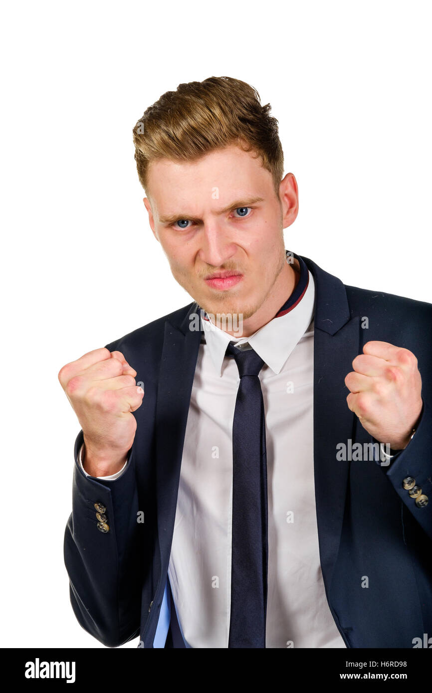 Aggressive angry young businessman raised hands and squeezed fists - Stock Image
