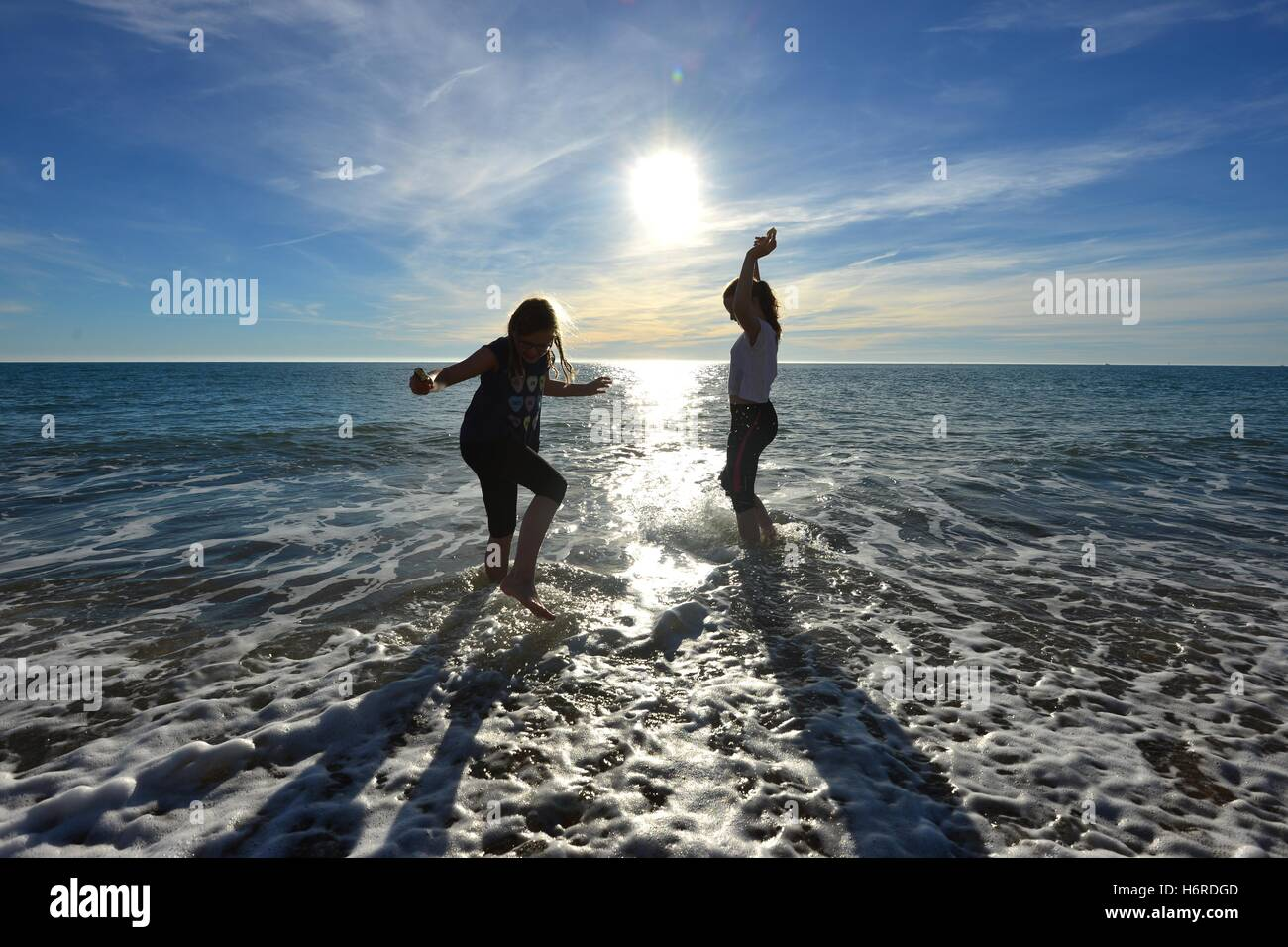 Seaford, Sussex, UK. 31st October, 2016. Children splashing in the sea with ice creams during unseasonably warm - Stock Image