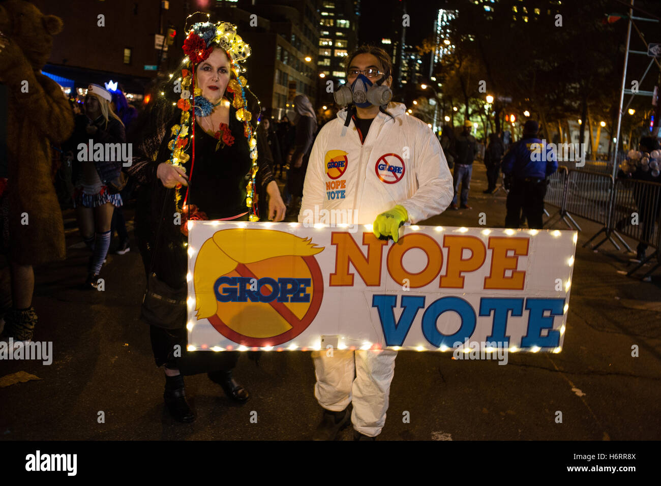 New York, NY - 31 October 2016. Two people walk behind a sign that reads Grope Nope Vote, the 'grope' behind - Stock Image
