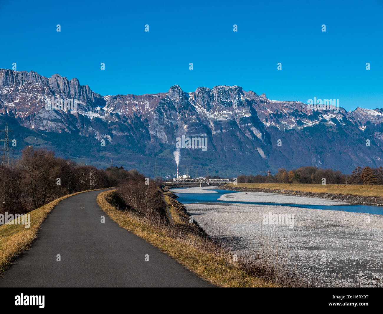 A road going along the damn of a rover - Stock Image