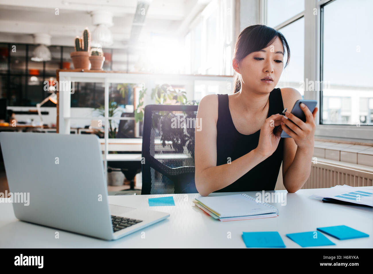Portrait of young asian woman sitting at her desk with laptop and adhesive notes using mobile phone. Asian businesswoman - Stock Image