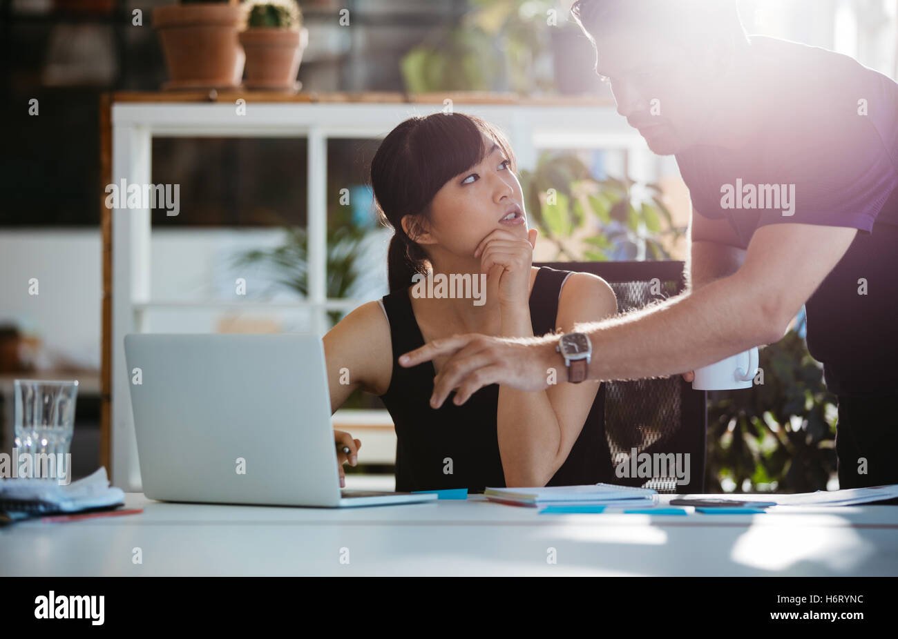 Shot of young asian woman sitting at her desk with man pointing at laptop. Two young executives working together - Stock Image