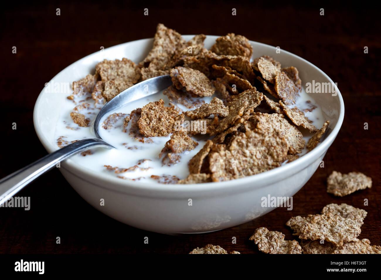 Half eaten wheat bran breakfast cereal with milk in ceramic