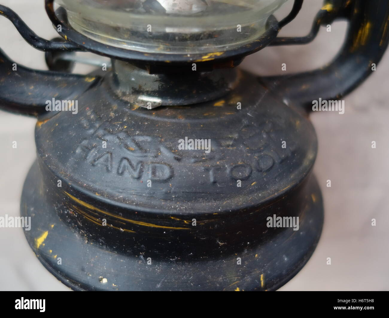 The bottom of an old lamp labeled 'hand tool' - Stock Image