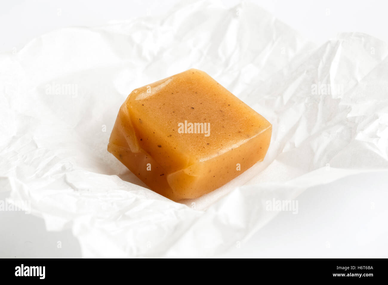 SIngle luxury unwrapped vanilla caramel toffee on white wrapper in perspective. - Stock Image