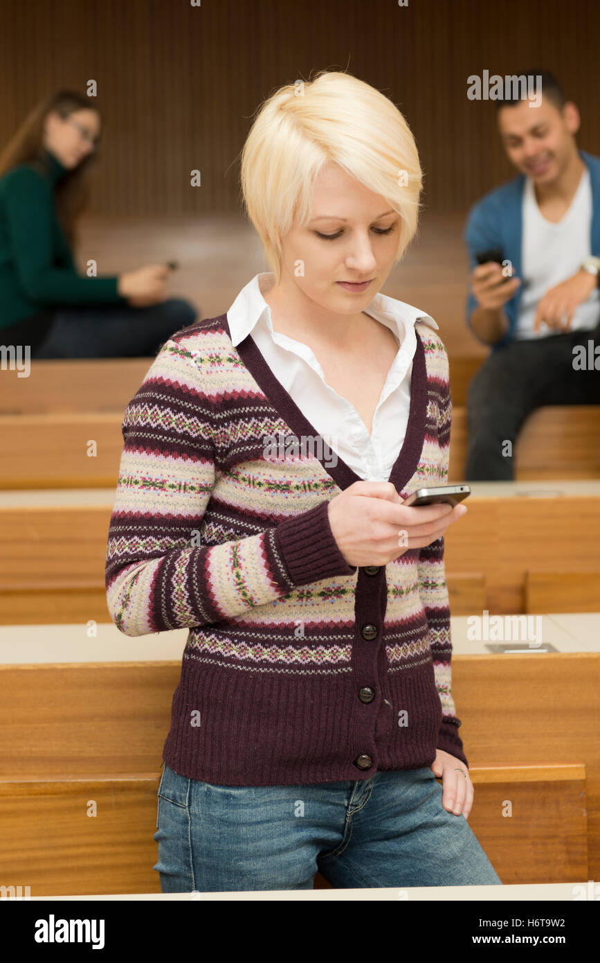 students interact with their phones - Stock Image