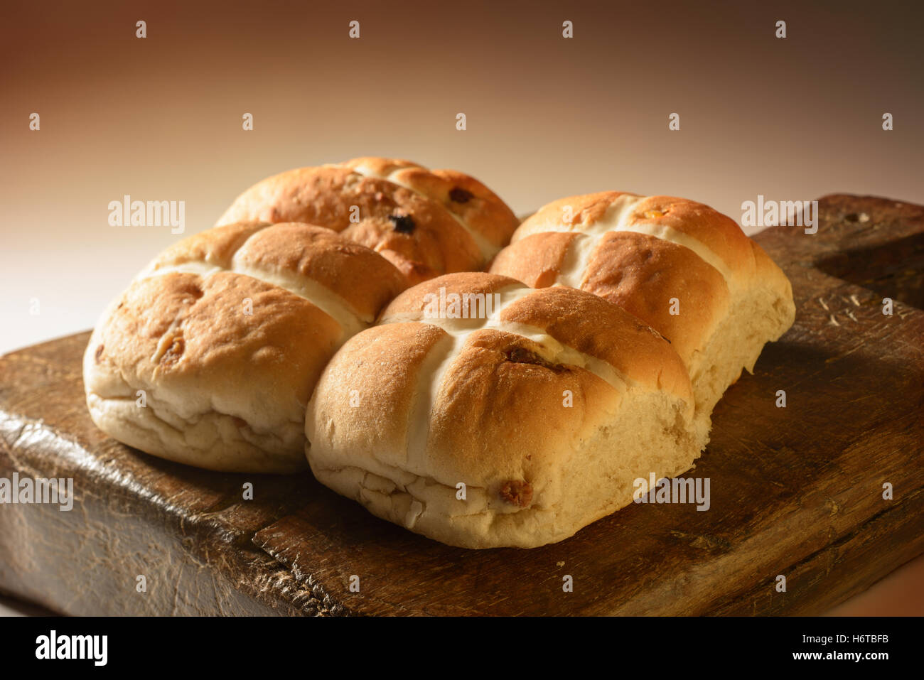 Creatively lit Hot Cross buns on rustic wooden board - Stock Image