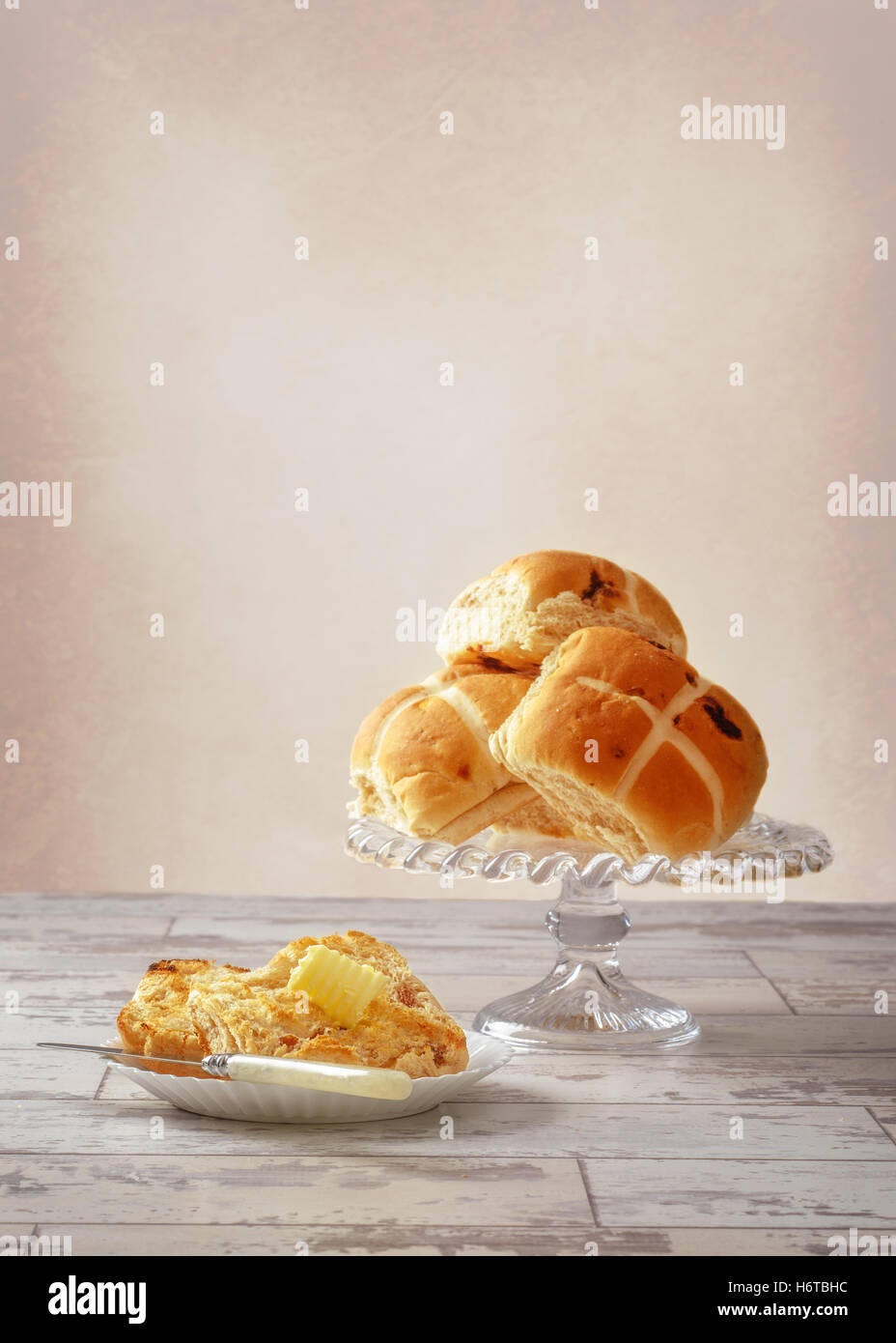Serving of hot cross bun with butter curl - Stock Image