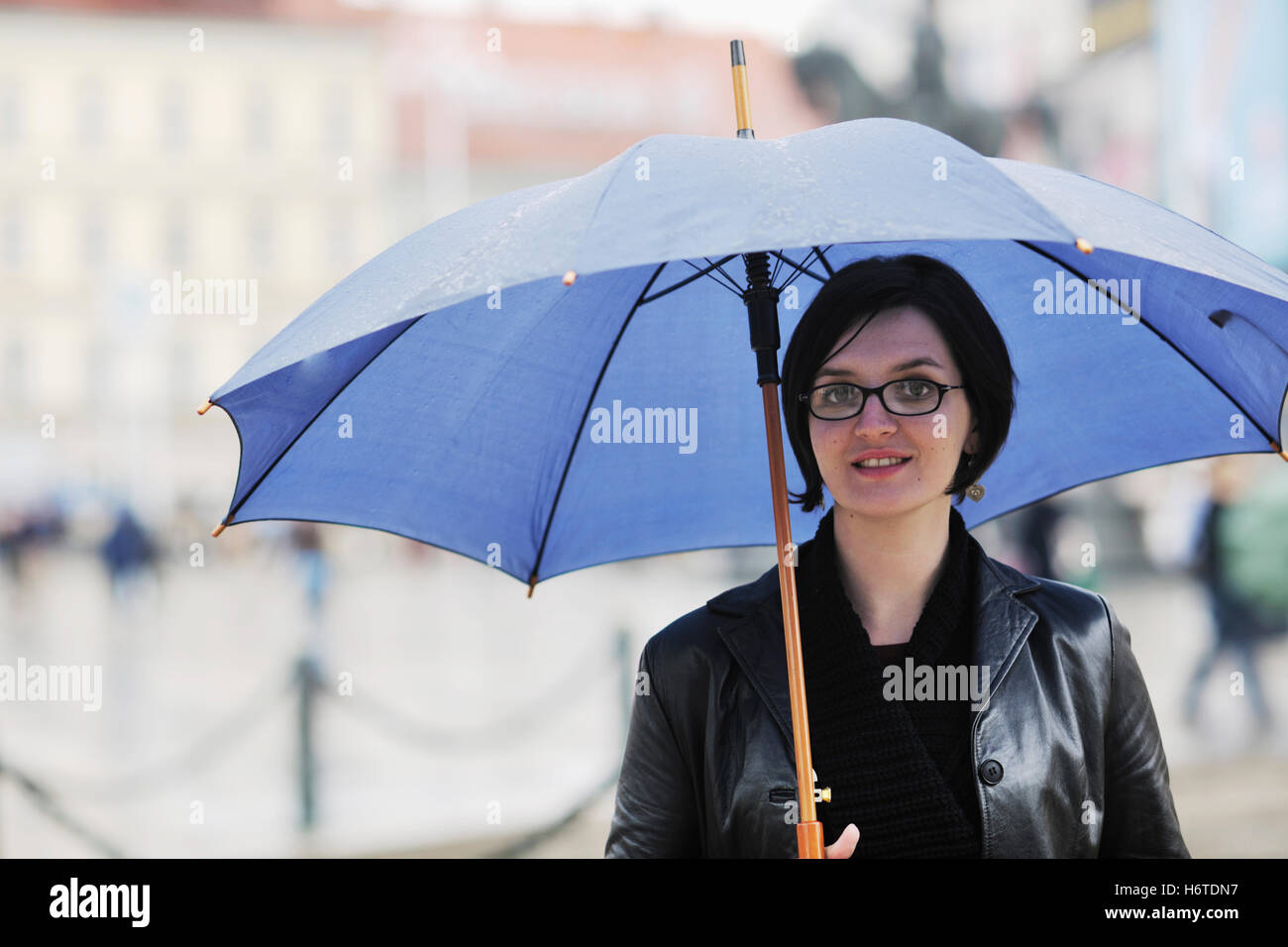 woman blue walk go going walking city town lady cloud umbrella spring bouncing bounces hop skipping frisks jumping - Stock Image