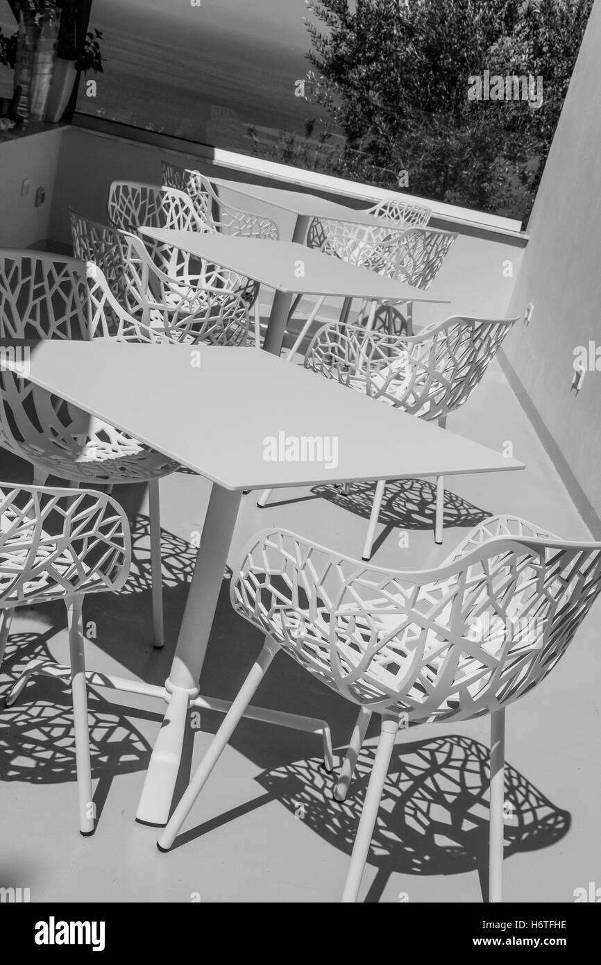 Round, retro, scene, seat, shadow, resting, restaurant, patio, pattern, peaceful, quiet, sitting, summer, weather, - Stock Image