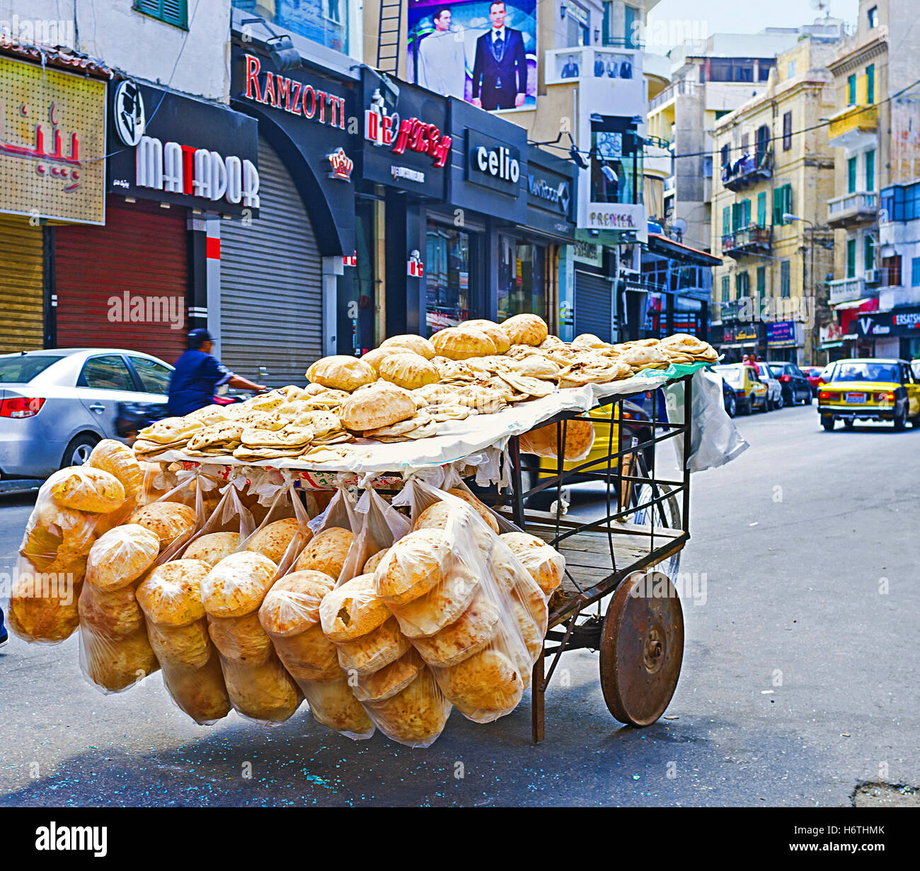 The old cart with the flat bread stands in the middle of the shopping street - Stock Image