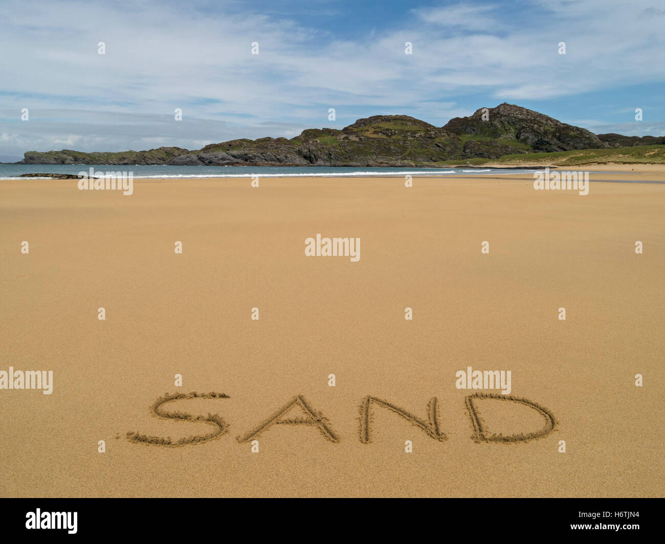 The word 'Sand' written in golden yellow sand of remote Scottish beach. - Stock Image