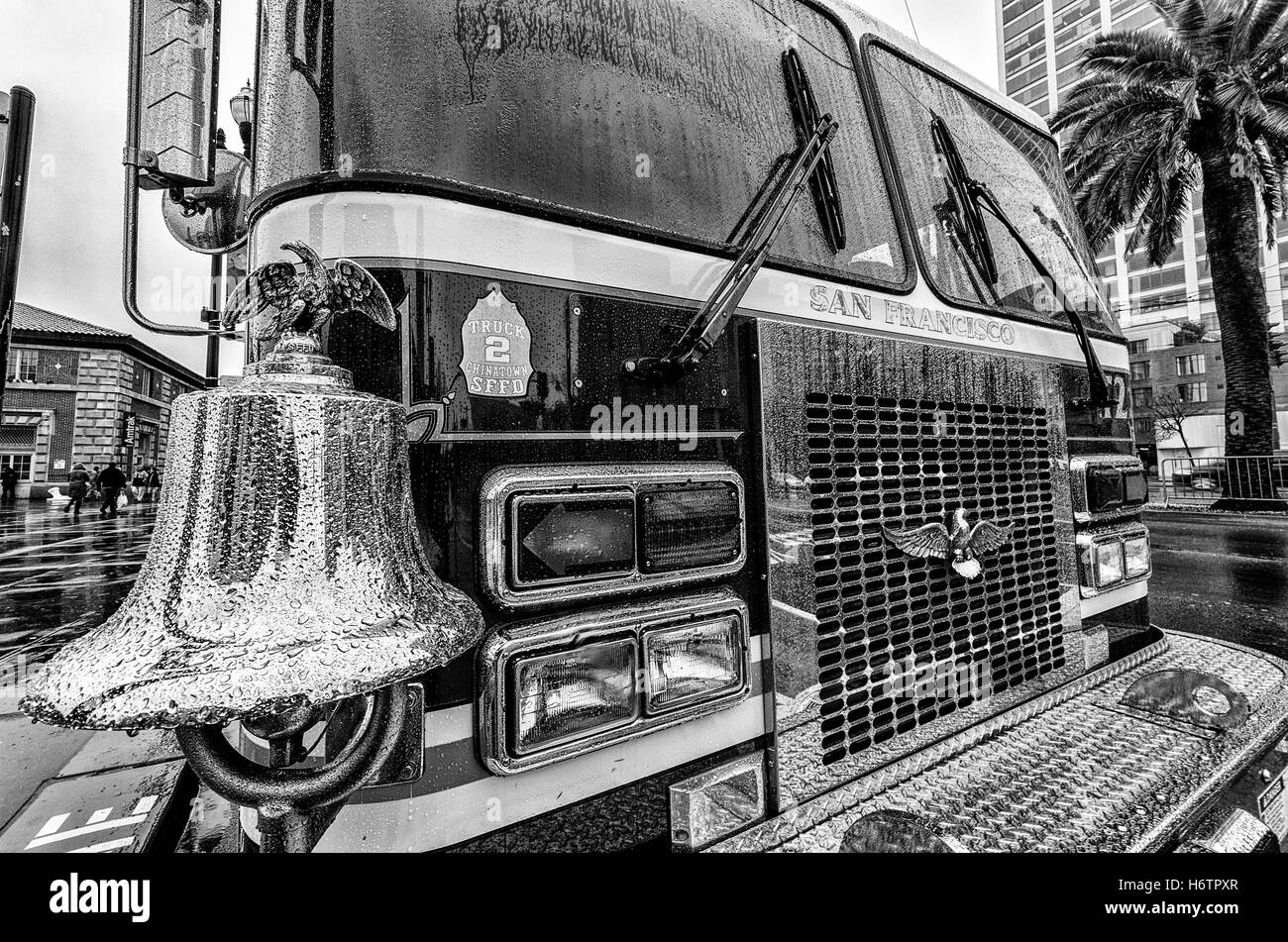 A bell adorns the front of a San Francisco ladder truck sitting in the rain on the Embarcadero. - Stock Image