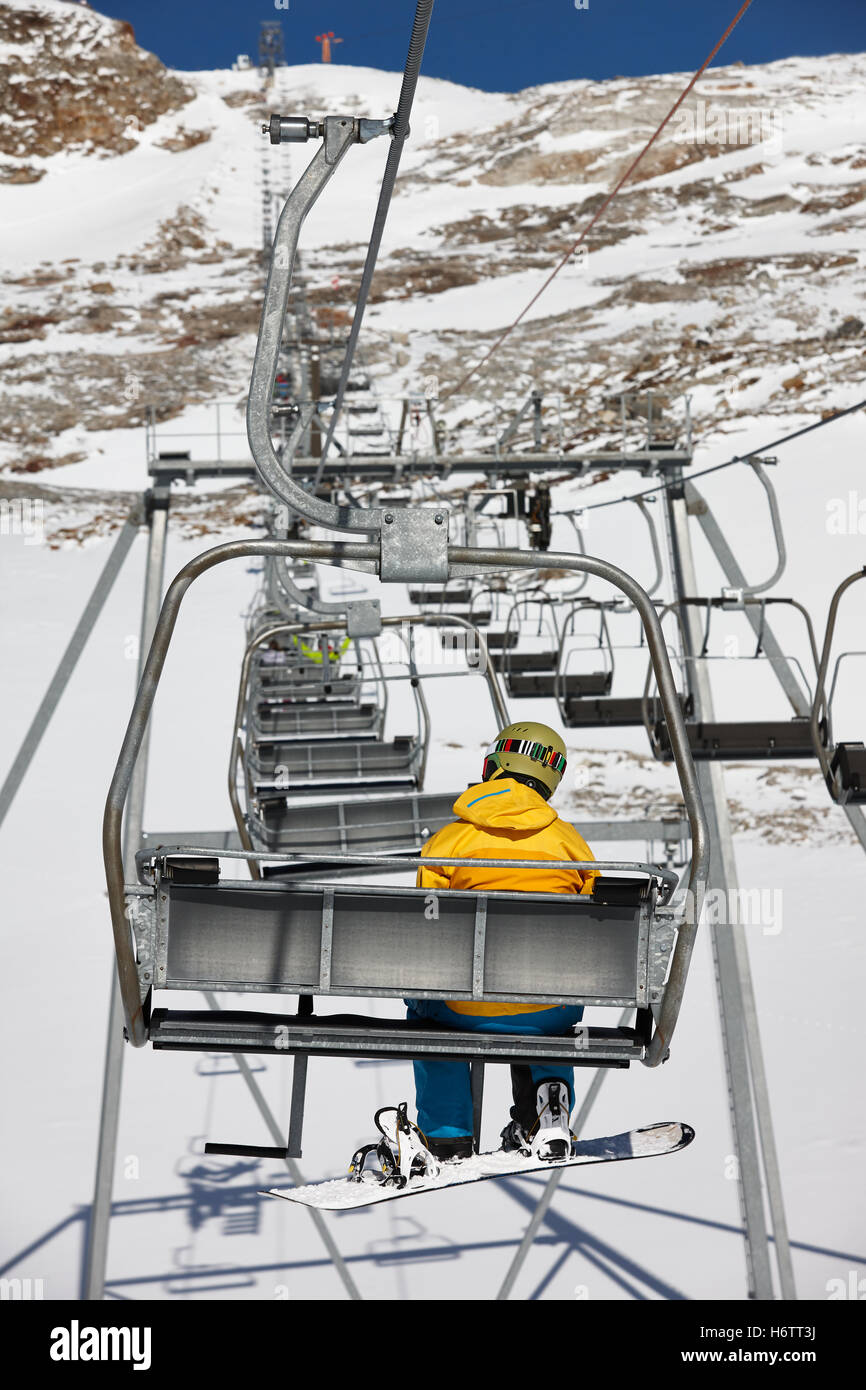 Snowboarder elevating on chairlift - Stock Image