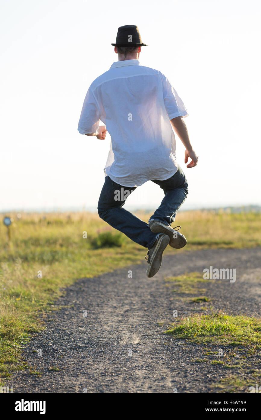 walk go going walking dust field spring bouncing bounces hop skipping frisks jumping jump bizarre business dealings - Stock Image