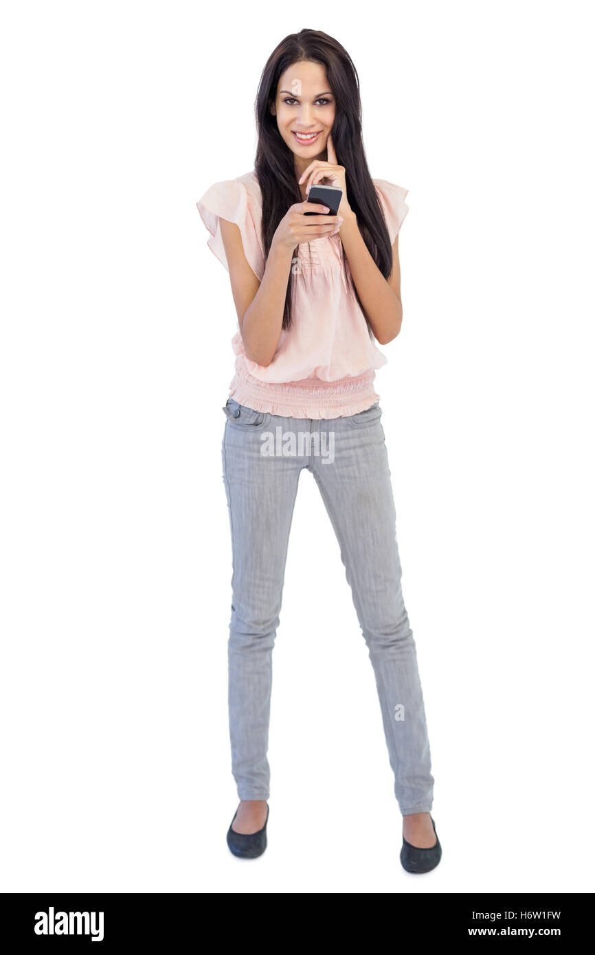 Smiling woman holding mobile phone on white background - Stock Image