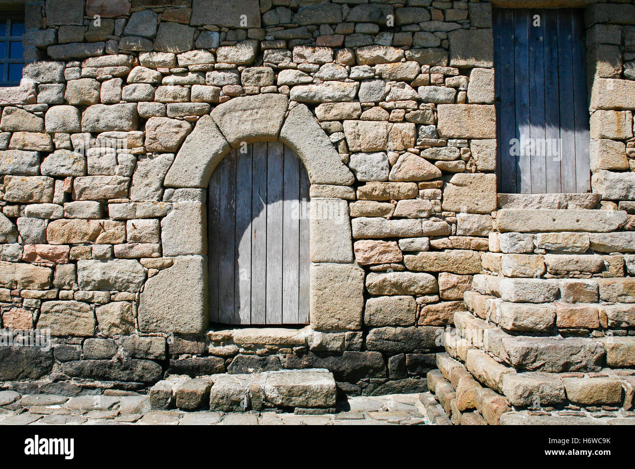 blue house building stone wood door summer summerly rock wall france coast traditional material drug anaesthetic - Stock Image