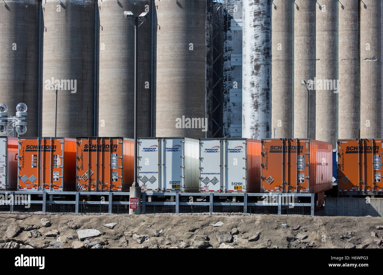 Grain silos with truck trailers in front of the silos. - Stock Image