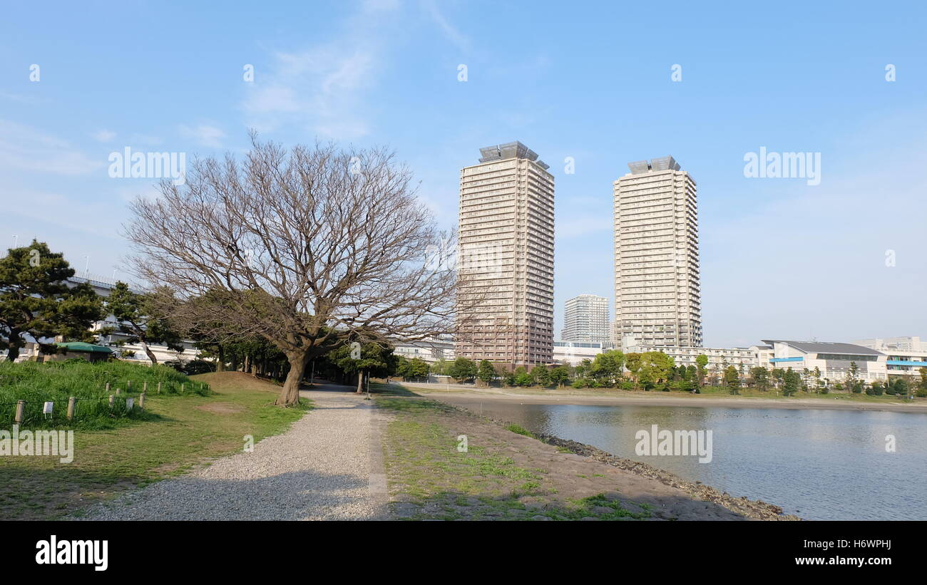 Outdoor on an early spring day with buildings, bare tree, path and bay - Stock Image