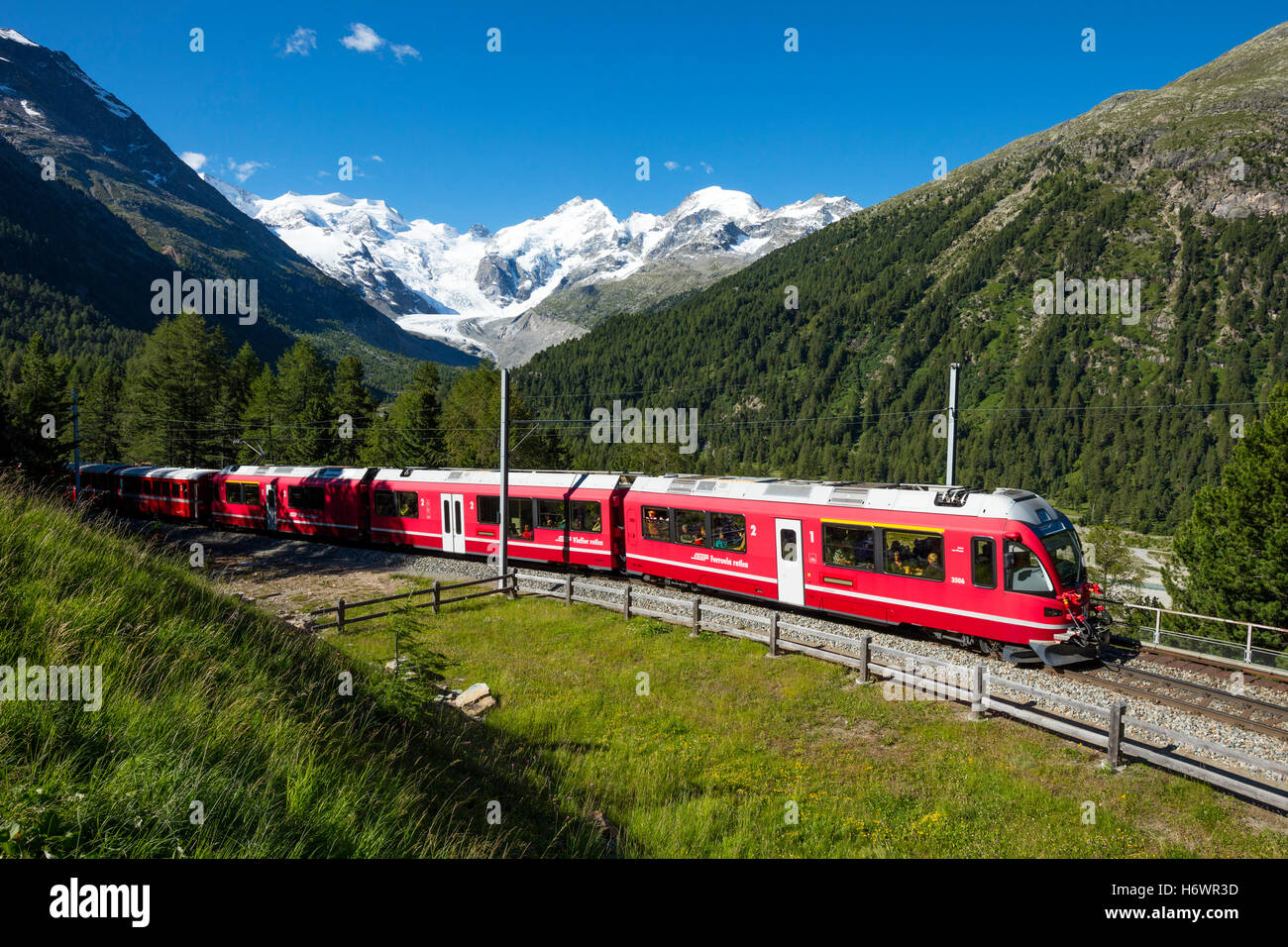 Bernina Express train beneath Morteratsch Glacier. Pontresina, Berniner Alps, Graubunden, Switzerland. - Stock Image