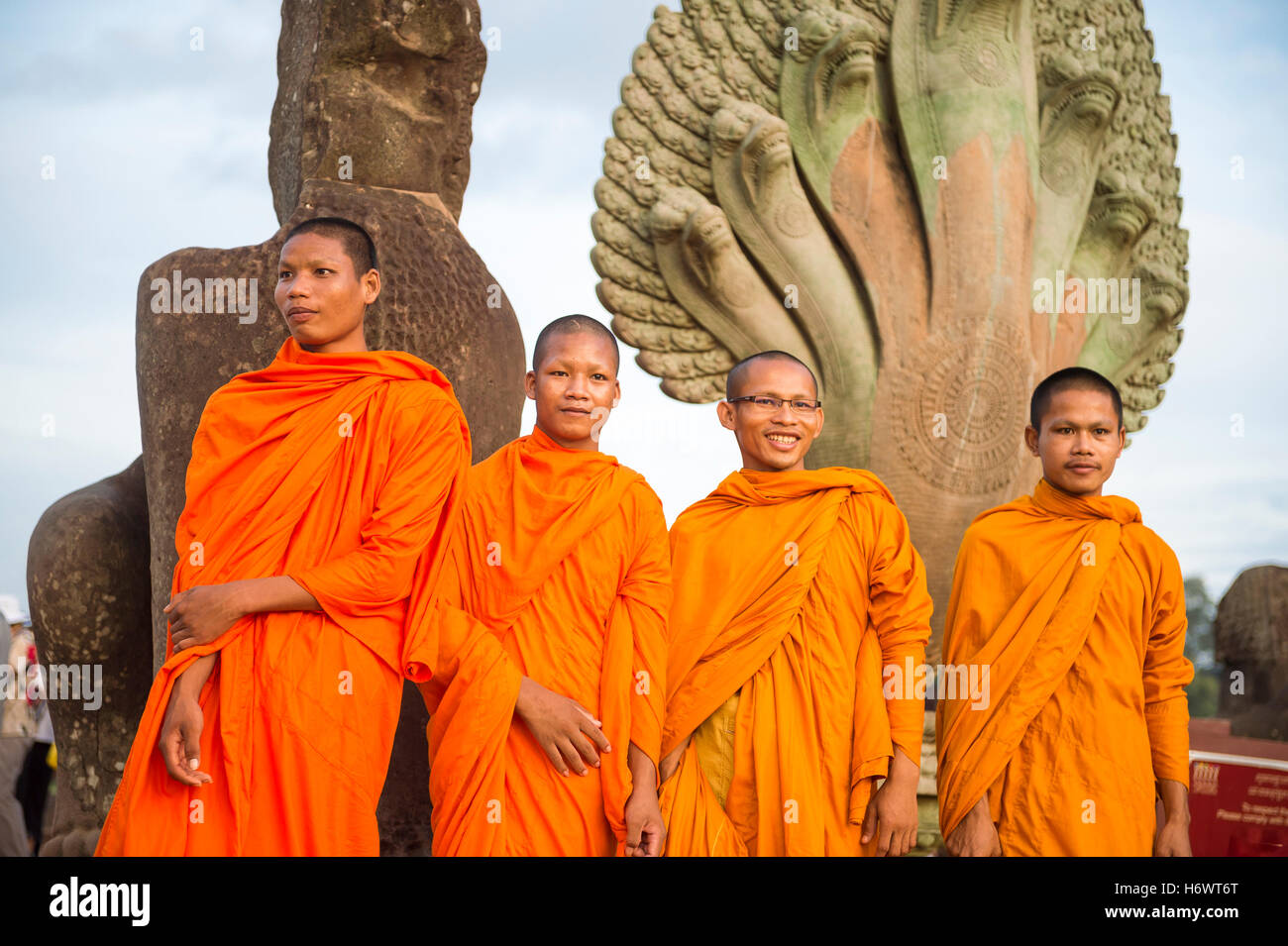 SIEM REAP, CAMBODIA - OCTOBER 30, 2014: Novice Buddhist monks in orange robes pose in front of the entrance to Angkor - Stock Image