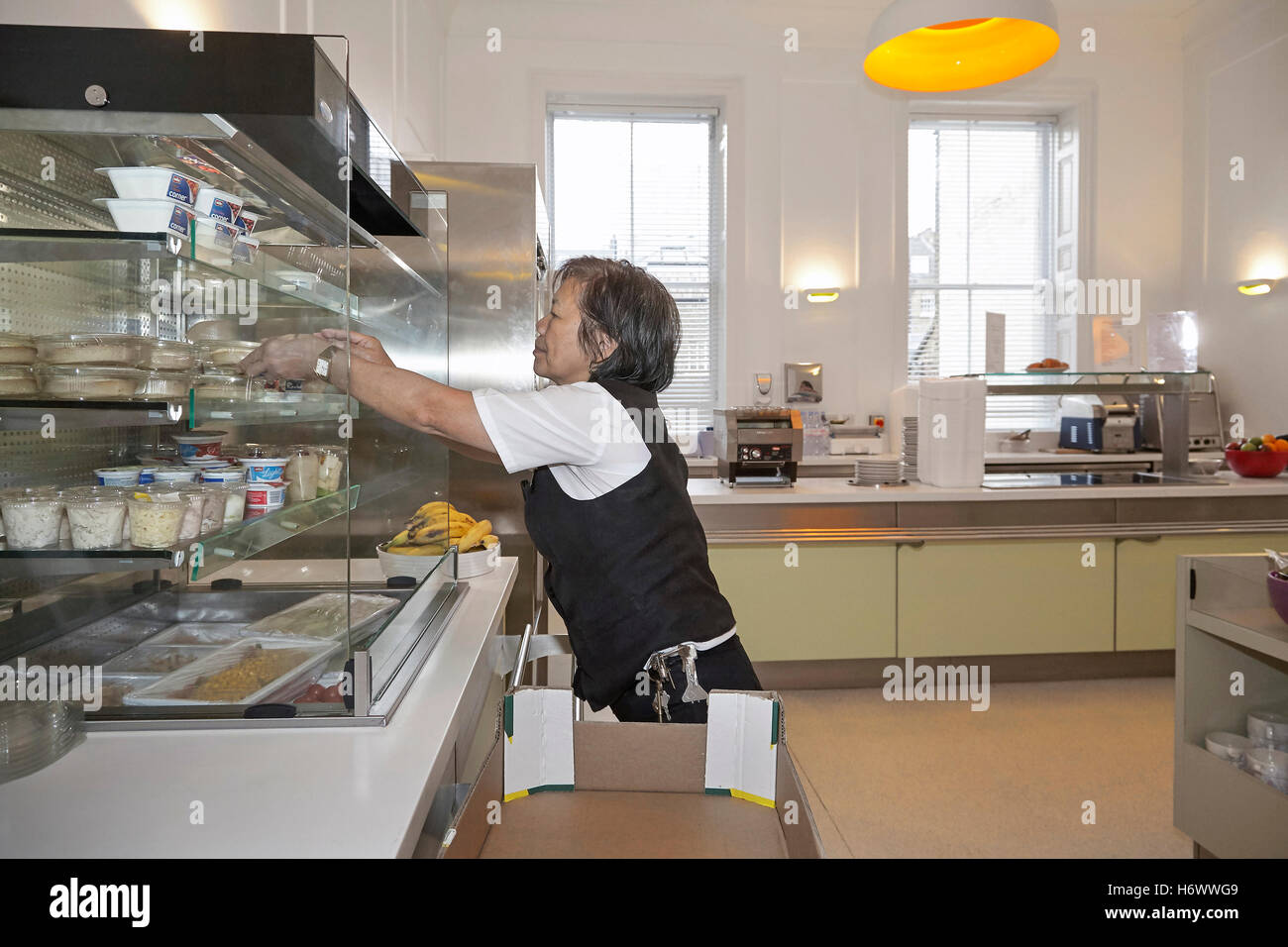 Kitchen worker, replenishing stock and tidying up in a works canteen. - Stock Image