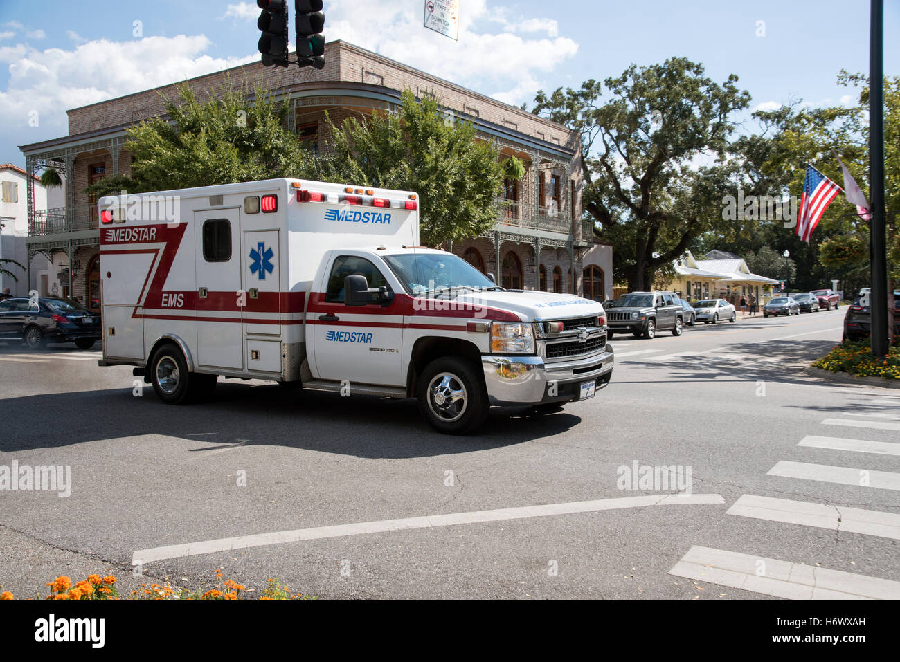 Downtown Fairhope Alabama USA  An ambulance on an emergency call traveling through the town center - Stock Image
