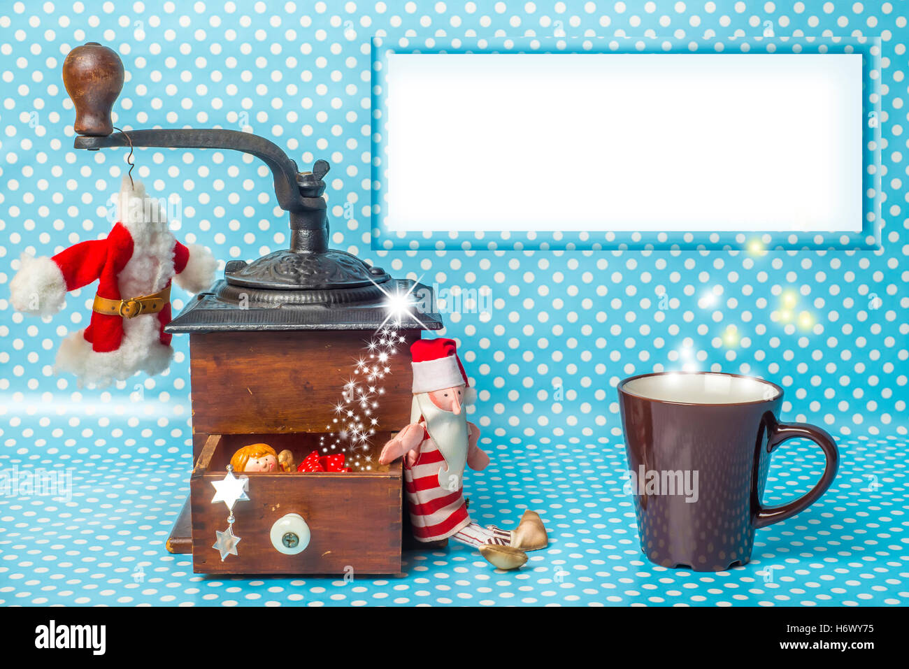 Christmas empty frame greeting card, vintage coffee grinder, cup of coffee Santa toy and Christmas decorations with - Stock Image