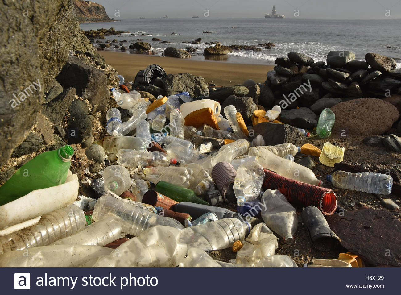 Collected plastic bottles, litter washed up on the shore and oil rig platform in background, Las Palmas Gran Canaria - Stock Image