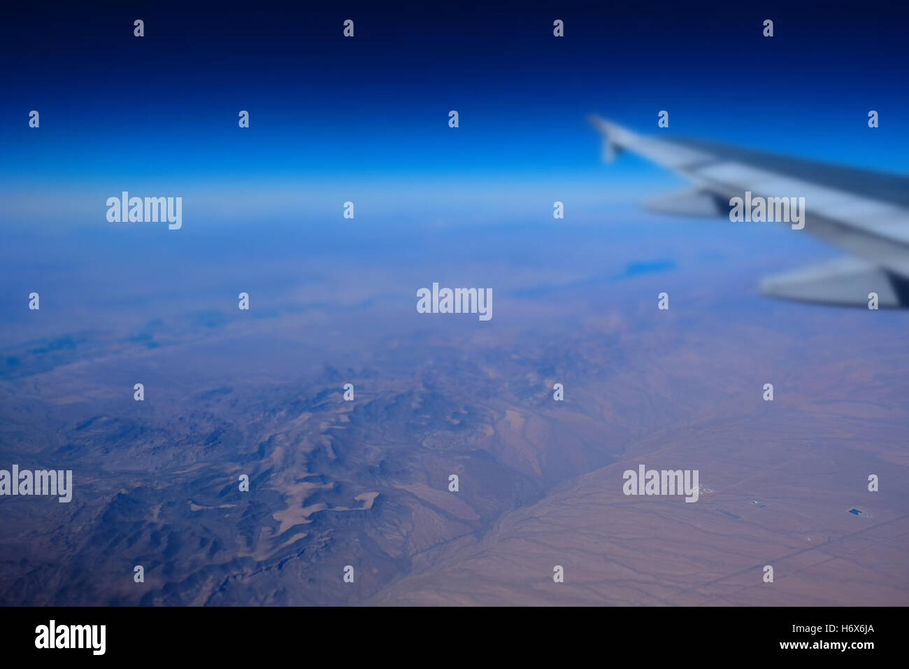 Airplane flying over desert mountains - Stock Image