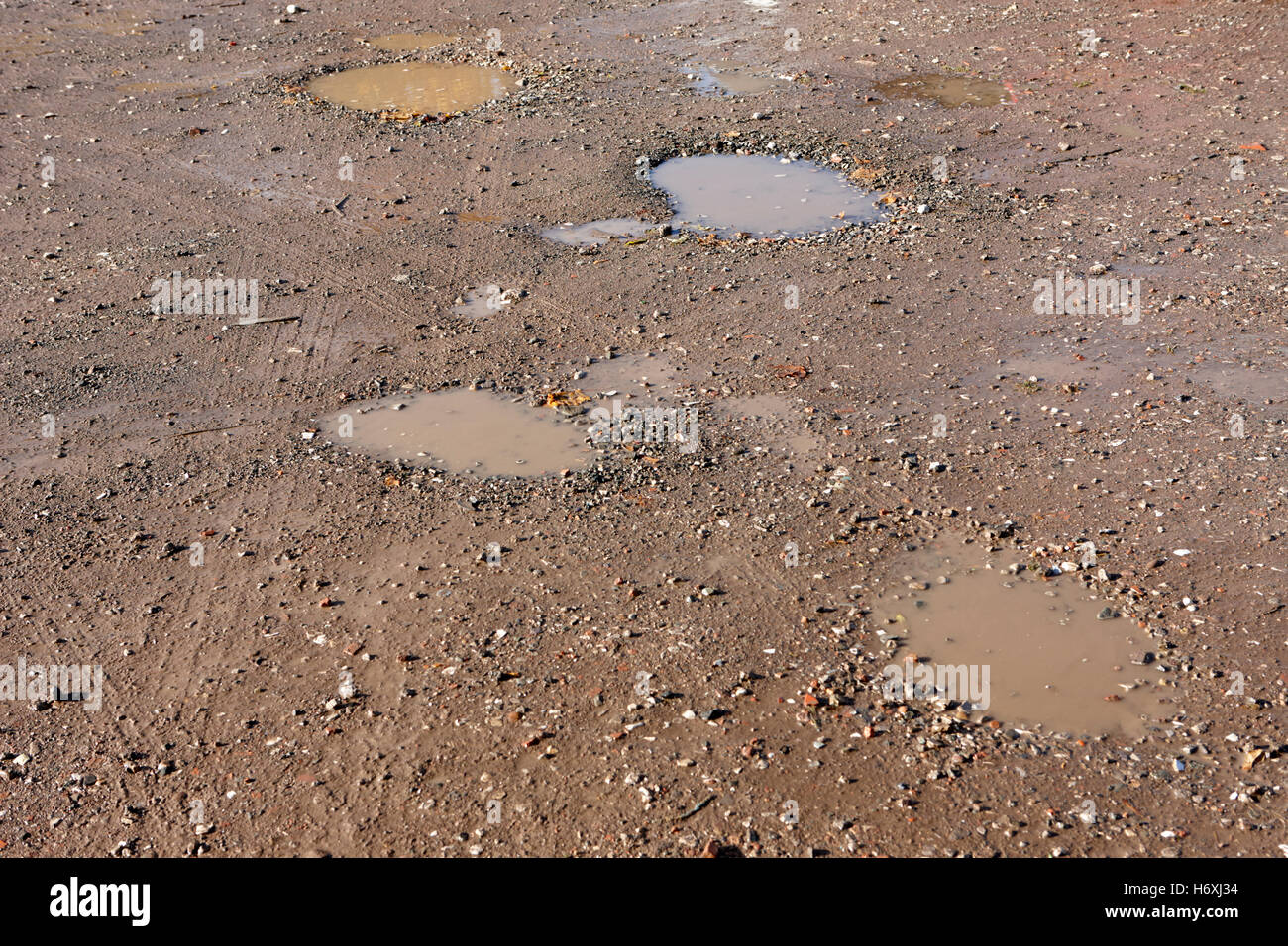 potholes in a rough gravel car parking area england uk - Stock Image