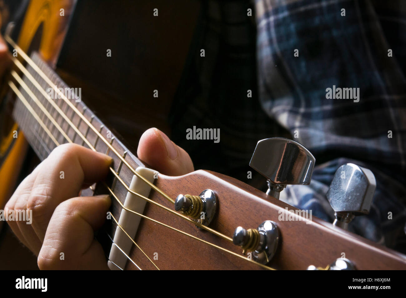 hand of a guitarist playing an acoustic guitar - Stock Image