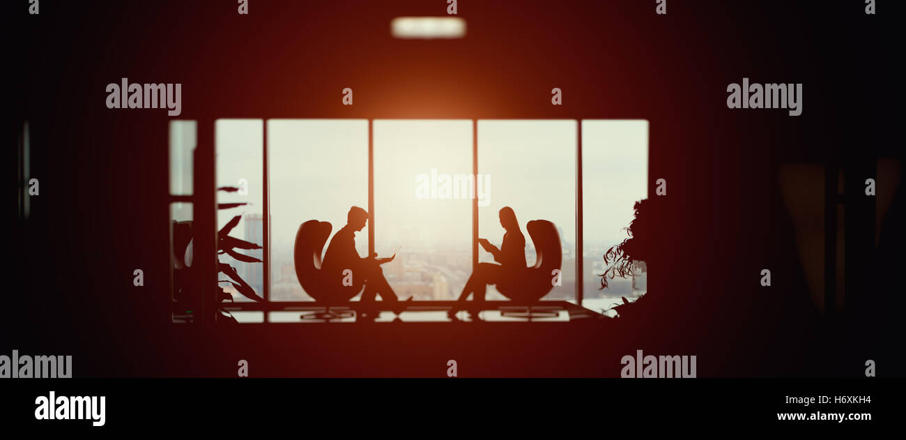 True tilt shift shooting of silhouettes of businessman and businesswoman sitting in front of each other with their - Stock Image