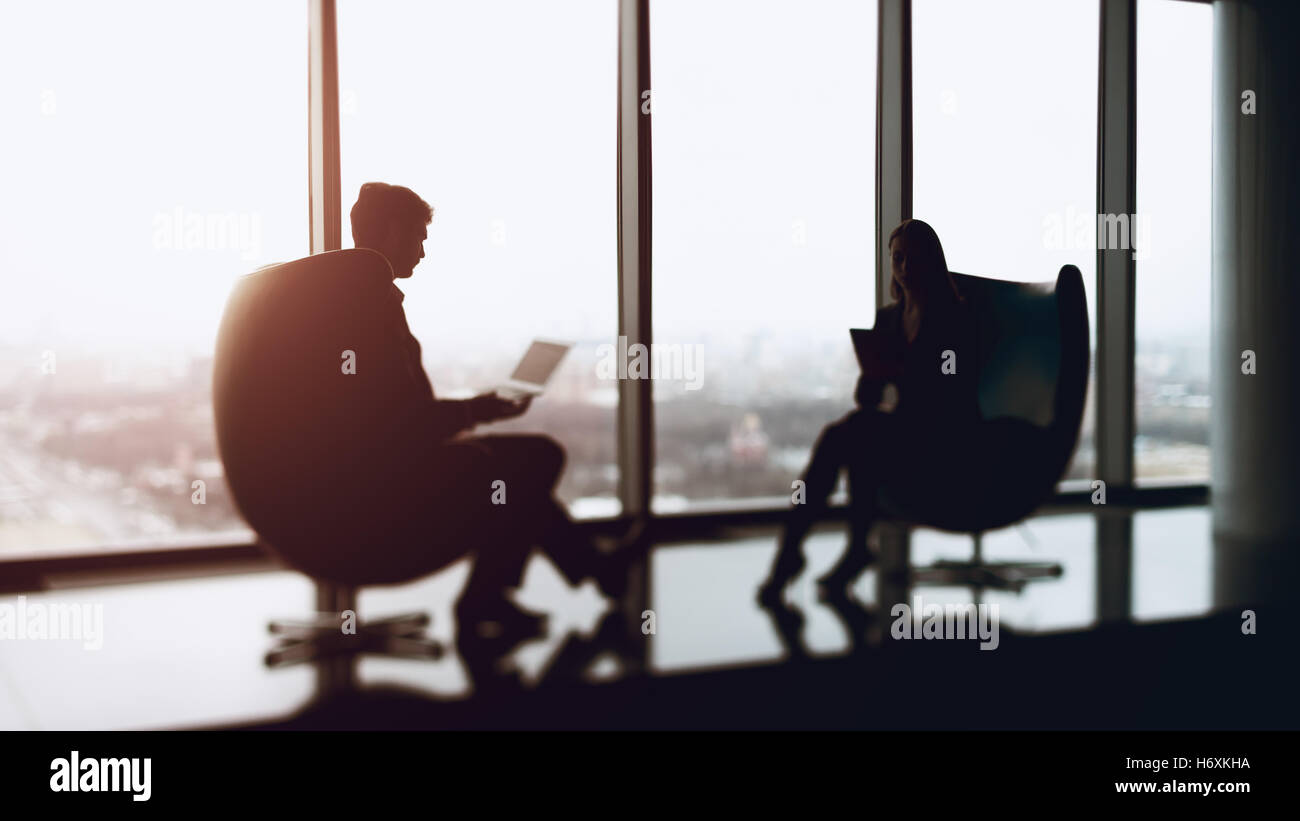 True tilt shift shooting of businessman with a laptop and businesswoman sitting in front of each other with their - Stock Image