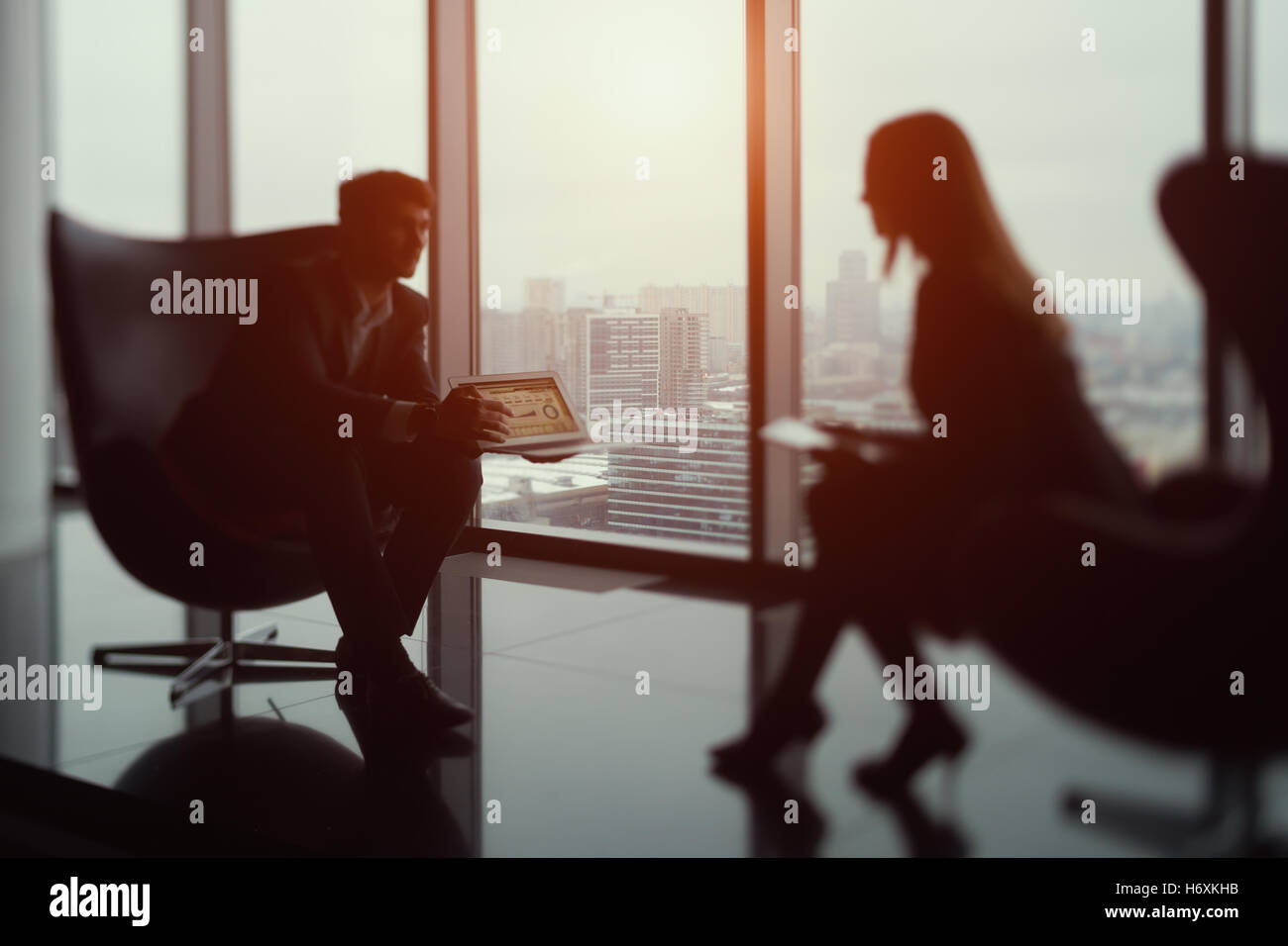 True tilt shift shooting of businessman sitting in front of his female colleague and showing diagrams on his laptop - Stock Image