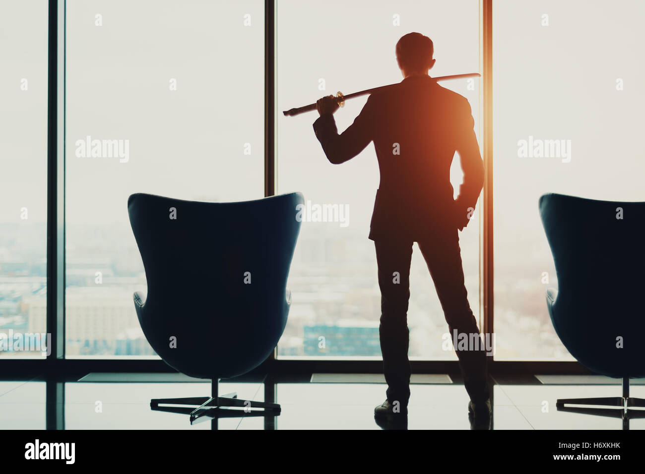 Young businessman in office in business suit standing between of two armchairs in front of window and holding katana - Stock Image