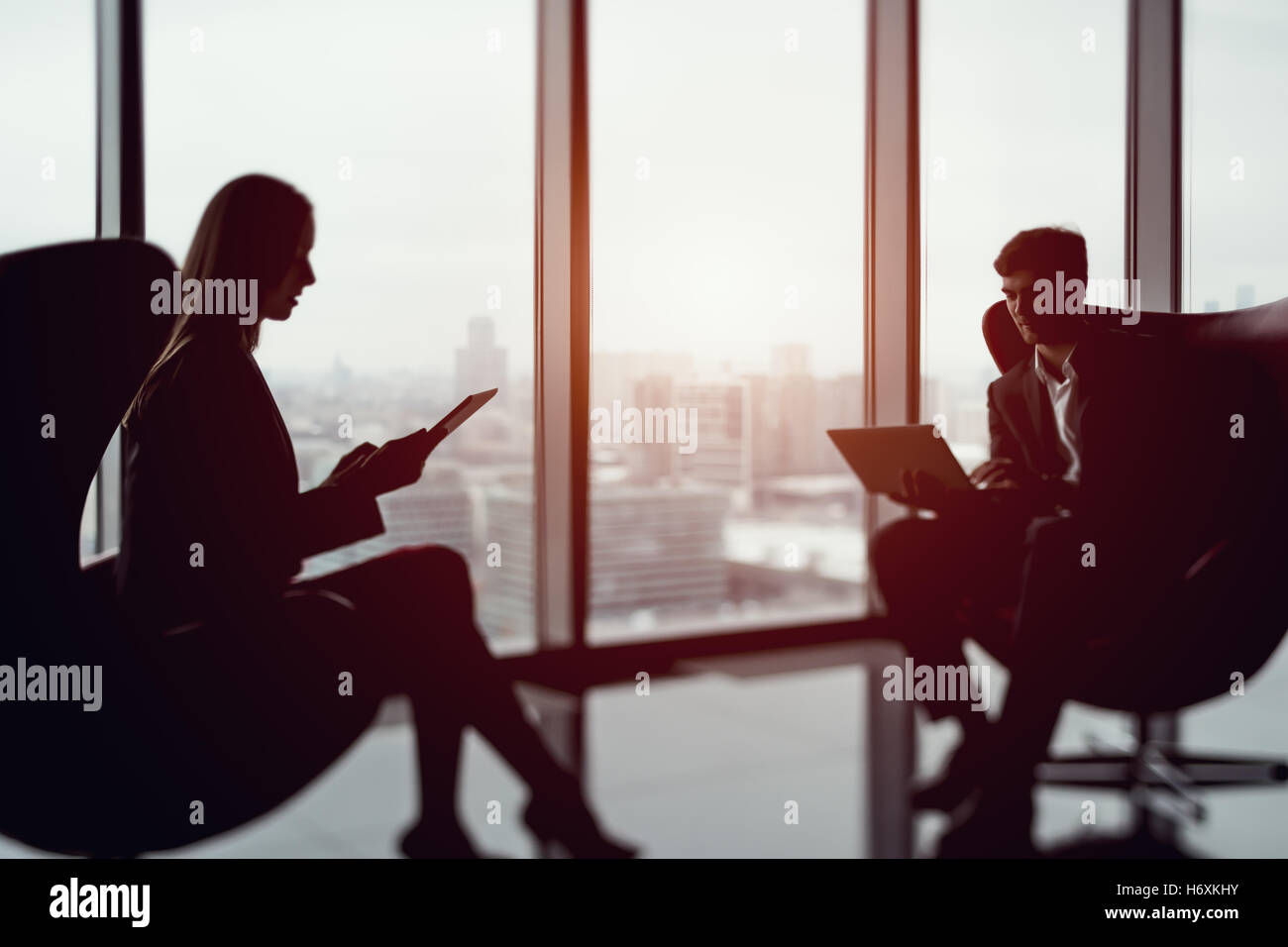 True tilt shift shooting of businessman with a laptop and businesswoman sitting in front of each other next to big - Stock Image