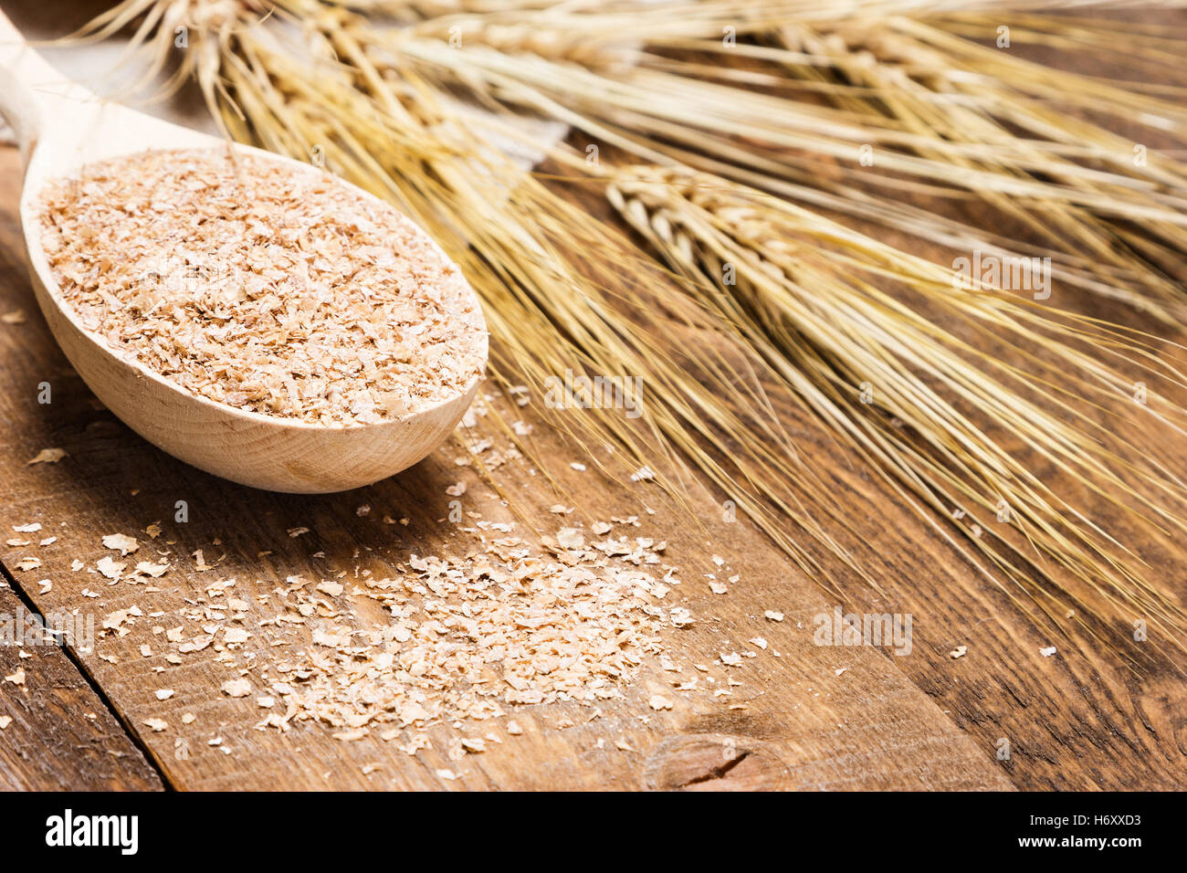 Close-up of wheat bran in wooden spoon with wheat ears. Dietary supplement to improve digestion. Source of dietary - Stock Image