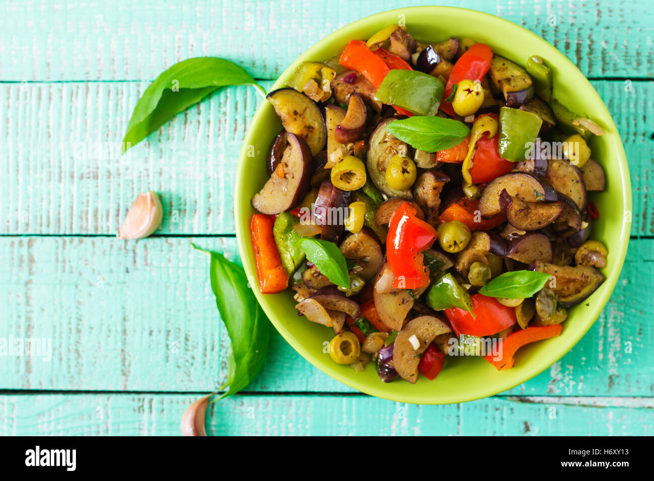Hot spicy stew eggplant, sweet pepper, olives and capers with basil leaves. Top view - Stock Image