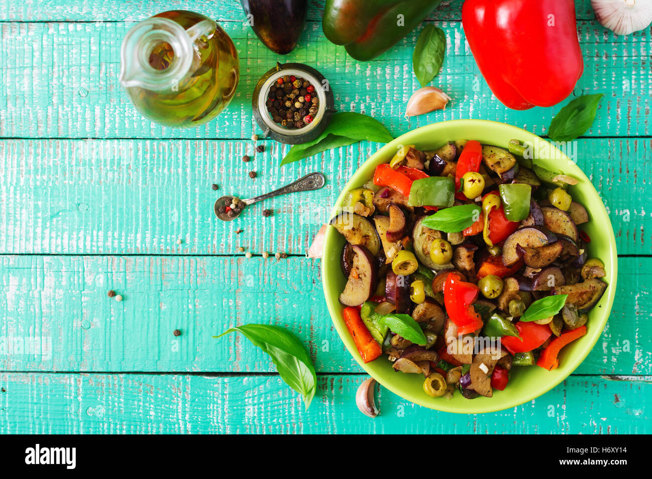 Hot spicy stew eggplant, sweet pepper, olives and capers with basil leaves. Top view Stock Photo