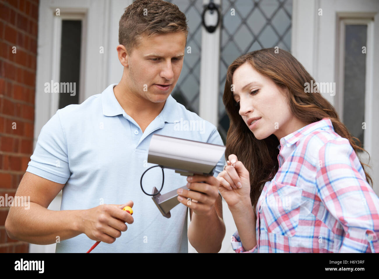Security Consultant Fitting Camera To Outside Of House - Stock Image