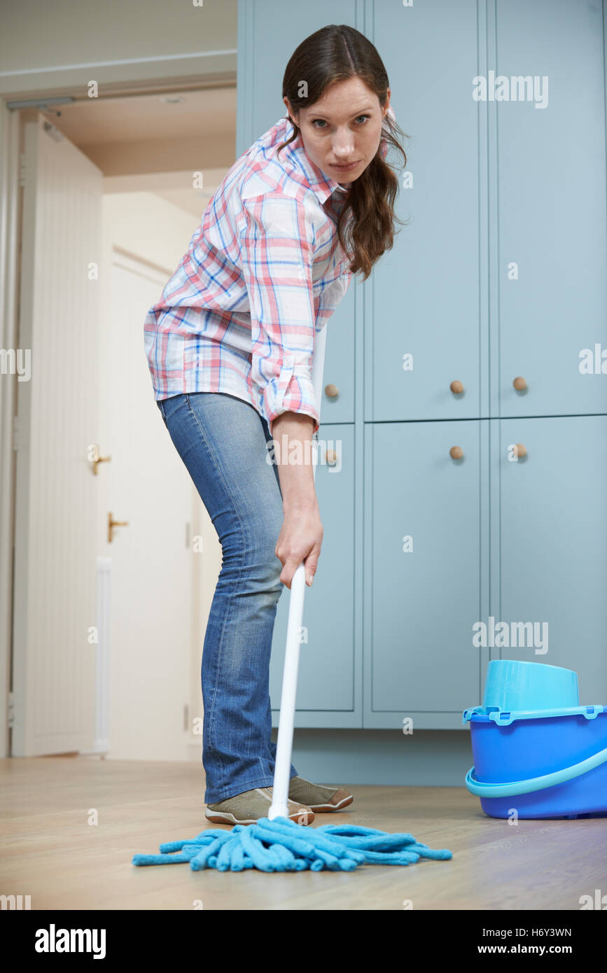 Unhappy Woman Cleaning Kitchen Floor With Mop - Stock Image