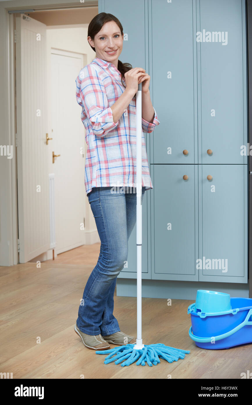 Portrait Of Woman Cleaning Kitchen Floor With Mop - Stock Image
