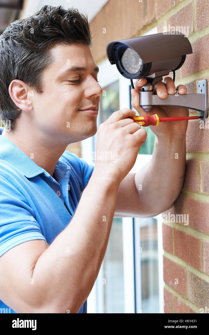 Security Consultant Fitting Camera To House Wall - Stock Image