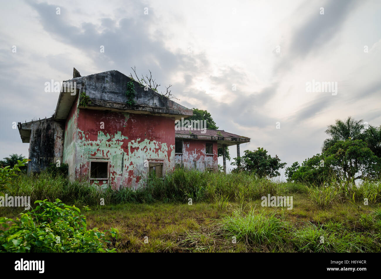 Ruined mansion surrounded by lush green with dramatic sky. Traces of the civil war in Liberia. - Stock Image
