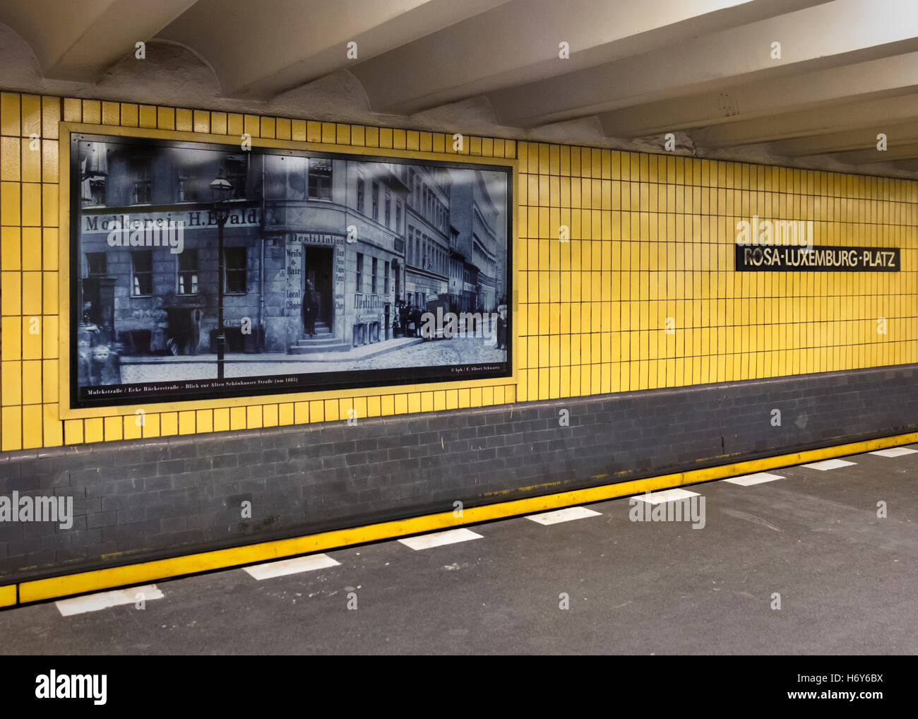 Berlin, Rosa-Luxemburg-Platz U-bahn U2 underground railway station with old monochrome photographs and yellow tiles - Stock Image